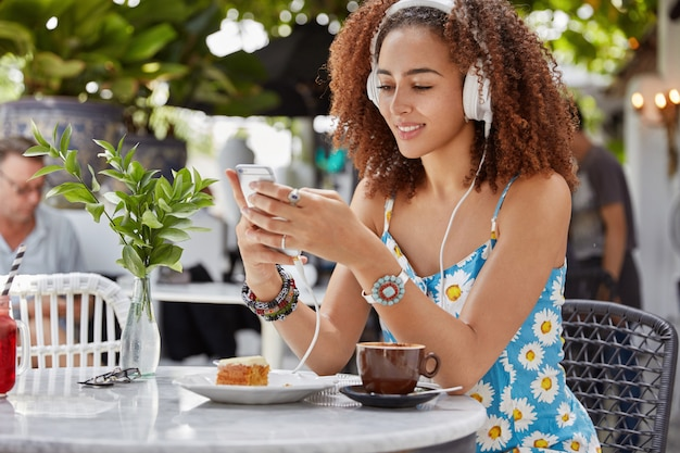Glad concnterated african american female enjoys favourite song from playlist, connected to smart phone and headphones, sits in outdoor coffee shop
