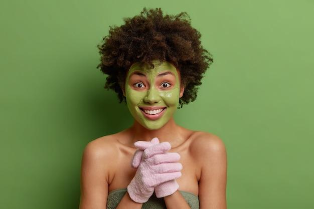 嬉しい巻き毛のアフロアメリカ人女性モデルが手を握りしめ、バスグローブを着用し、顔に緑色のマスクを適用して、屋内のタオルに包まれた肌のポーズを若返らせます