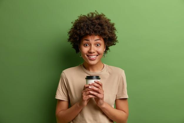 Felice donna afro-americana dai capelli ricci beve caffè aromatico dalla tazza usa e getta, ha una conversazione felice interessante, sorride a trentadue denti, indossa abiti casual, isolato su un muro verde vivido