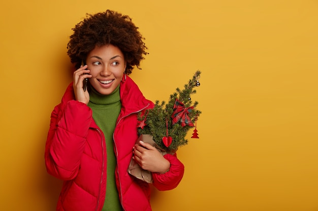 Glad curly haired woman has phone talk, holds small decorated firtree for christmas