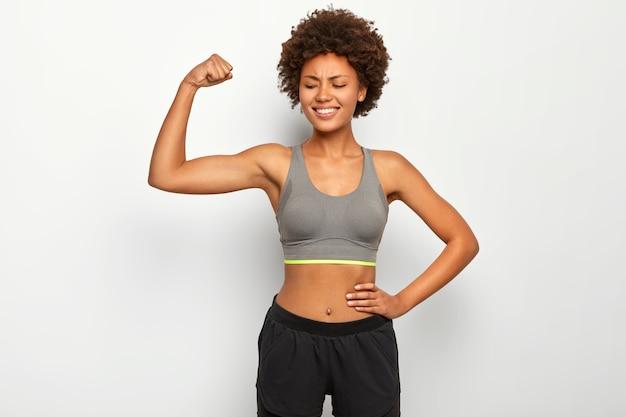 기쁜 곱슬 머리 여자는 팔을 들어 올리고, 팔뚝을 보여주고, 근육을 보여주고, 날씬한 몸매를 가지고, 캐주얼 탑과 반바지를 입고, 흰 벽 위에 모델을 입습니다.