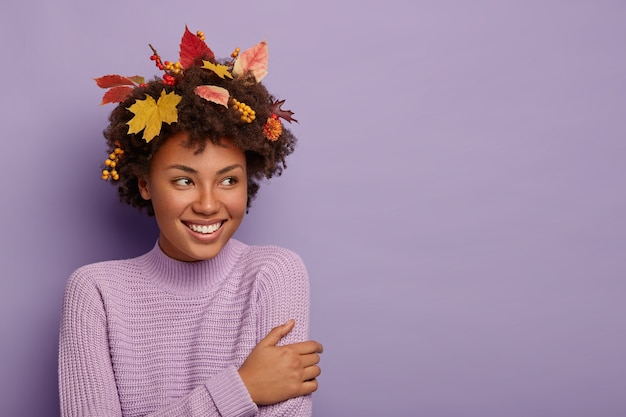 Glad curly haired woman turns aside, has joyful gaze, being pleased by something awesome, wears casual outfit, maple leaves on head, smiles pleasantly, poses indoor