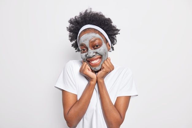 Glad curly haired young woman enjoys daily beauty procedures keeps hands under chin smiles gently applies clay mask to rejuvenate skin