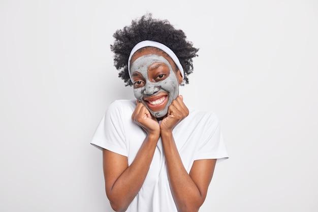 Довольная кудрявая молодая женщина наслаждается ежедневными косметическими процедурами, держит руки под подбородком и улыбается, нежно наносит глиняную маску для омоложения кожи.