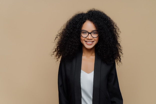 Glad curly haired young woman with toothy smile