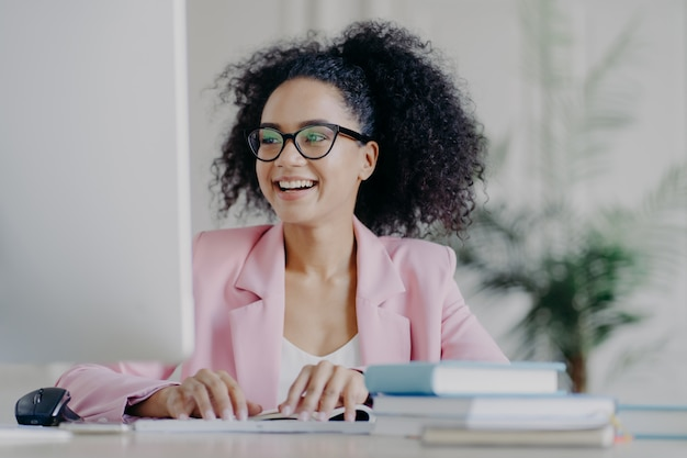 Glad curly professional female manager focused into computer screen, smiles broadly, has curly hair, wears transparent glasses, elegant suit, poses at desktop in her cabinet, works remotely