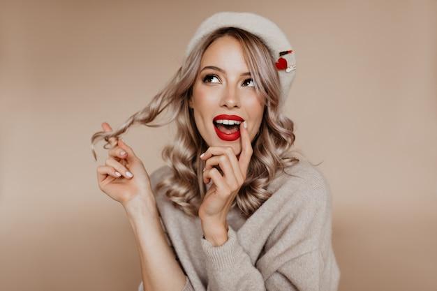 Felice donna riccia in berretto francese seduto sul muro marrone