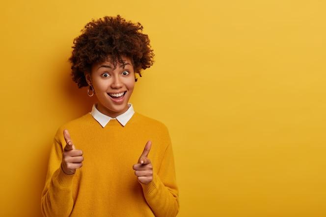 嬉しい巻き毛の女性はあなたに両方の人差し指を向け、銃のサインを示しています