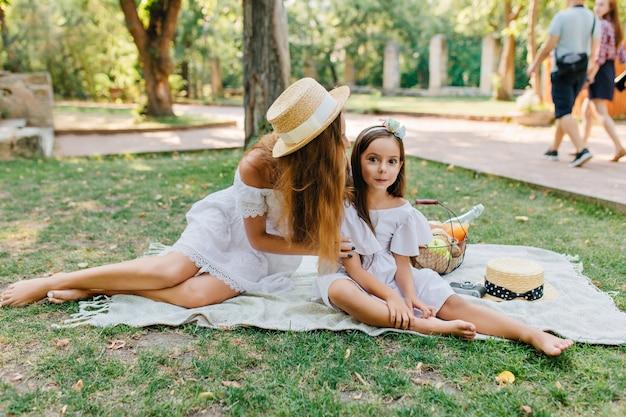 嬉しい黒髪の女の子が母親の近くの毛布の上に座って、彼女の足に触れています。ファッショナブルな若い女性と人々と草の上でポーズをとる白いドレスのかわいい娘の屋外家族の肖像画。