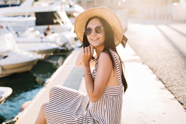 Радостная темноволосая дама в шляпе проводит время в морском порту, наслаждаясь солнцем в солнечный день где-то в европе