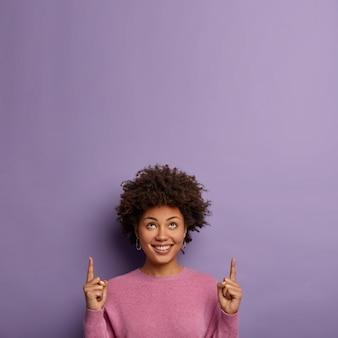기쁜 어두운 피부 아프리카 계 미국인 여성이 빈 공간을 가리 킵니다.