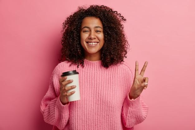 Felice modello femminile riccio dalla pelle scura fa un gesto di pace, tiene il caffè da asporto, si diverte durante la pausa, sorride alla telecamera, indossa un maglione, posa su un muro roseo.