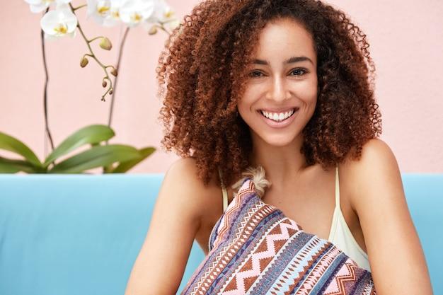 Радостная темнокожая кудрявая женщина с широкой сияющей улыбкой обнимает подушку, сидя на удобном диване у розовой стены.