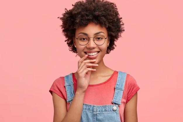 ピンクの壁に隔離された、デニムのオーバーオールが付いたカジュアルなtシャツを着た、心地よい笑顔のうれしい暗い肌の巻き毛の女性。