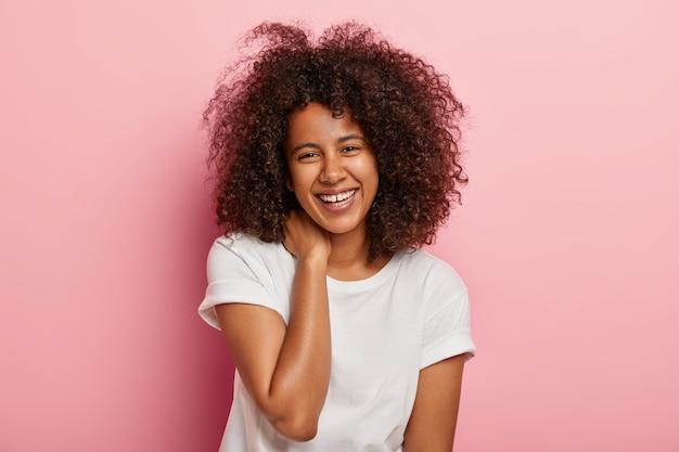 嬉しい暗い肌の女性は、面白い会話をし、広い笑顔で見え、友人に楽しまれ、表情を大喜びし、普段着を着て、屋内に立っています。感情の概念