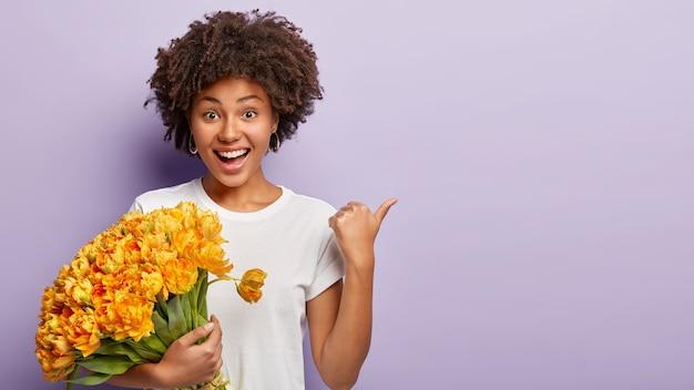 Felice modello femminile dalla pelle scura punta da parte su uno spazio vuoto, tiene un mazzo di tulipani arancioni primaverili