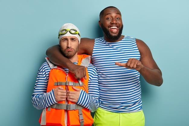 Радостный темнокожий парень обнимает грустного товарища и говорит, что посмотрите на этого парня, который не умеет плавать.