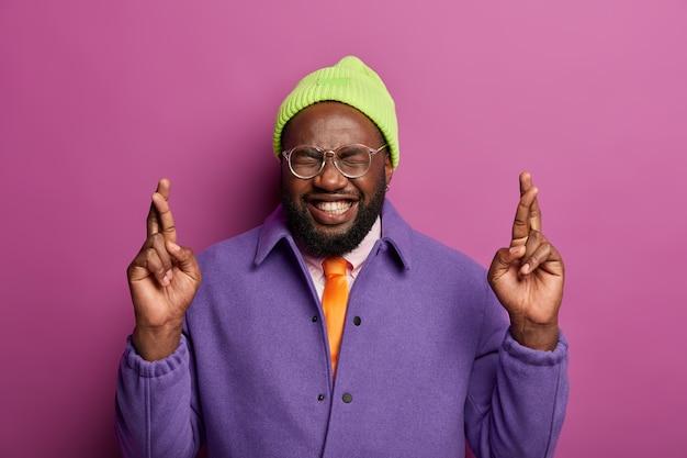 Довольный темнокожий парень стоит со скрещенными пальцами, желает лучшего, зубасто улыбается, носит шляпу и пурпурный пиджак, он суеверен.