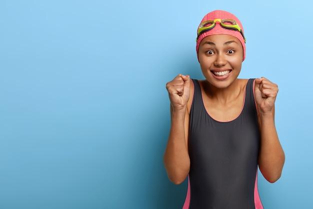 Радостный темнокожий здоровый пловец сжимает кулаки и делает торжественный жест