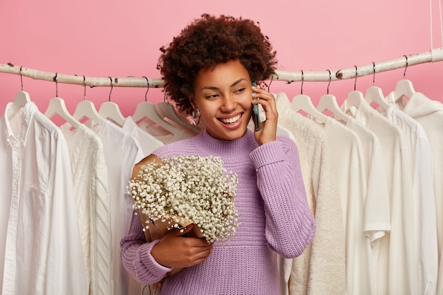 Glad dark skinned lady holds mobile phone, stands with bouquet near rack filled of clothes, dressed in purple knitted sweater, isolated over pink background.