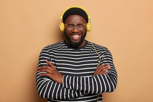 嬉しい暗い肌の男は幸せに笑い、腕を組んで、縞模様のジャンパーを着ています