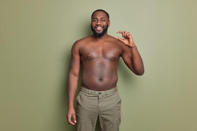 기쁜 어두운 피부를 가진 남자가 벌거 벗은 몸통으로 포즈를 취하고 작은 제스처를 만듭니다.