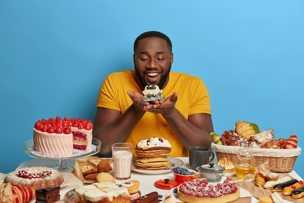 Felice ragazzo dalla pelle scura goloso tiene un piccolo cupcake, guarda felicemente un delizioso dessert, indossa una maglietta gialla, posa su sfondo blu