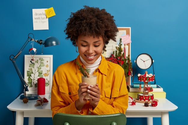 에그 노그 칵테일을 맛보고 기쁜 어두운 피부를 가진 여자, 즐겁게 미소 짓고, 크리스마스 휴가를 기다리고, 램프가있는 흰색 책상 근처의 의자에 포즈, 시계, 장식 된 전나무 나무, 축제 분위기가 있습니다.