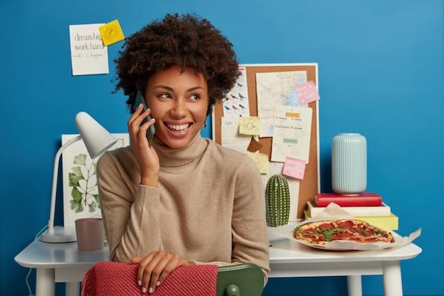 기쁜 어두운 피부를 가진 여성이 전화 통화를하고, 외모를 보며, 완성 된 작업으로 기분이 좋으며, 노트북 더미, 벽과 보드에 스티커 메모, 맛있는 피자와 함께 바탕 화면에 앉아 있습니다.