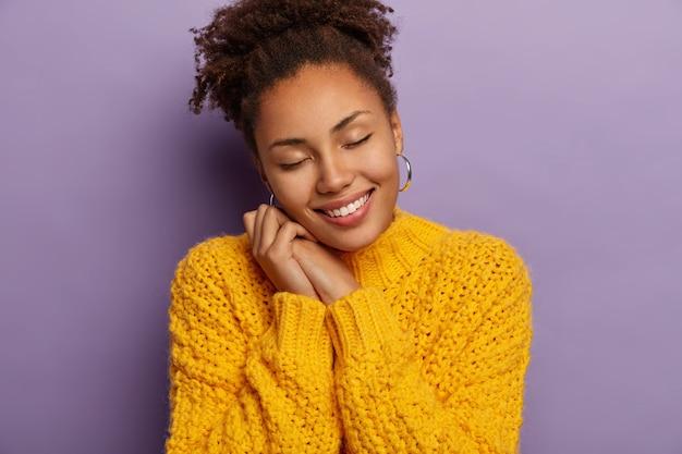 두 손에 기대어 기쁜 어두운 피부를 가진 여자, 눈을 감고, 노란색 니트 스웨터를 입고, 보라색 스튜디오 벽 위에 모델