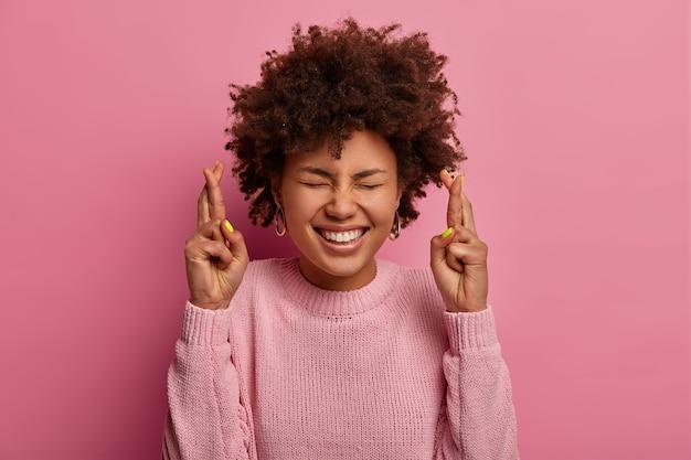 嬉しい暗い肌の女性は、交差した指で立って、重要なニュースを予期し、屋内でジェスチャーをし、巻き毛を持ち、カジュアルなジャンパーを着て、甘い欲望を作り、ピンクの壁に隔離されています。ボディランゲージ