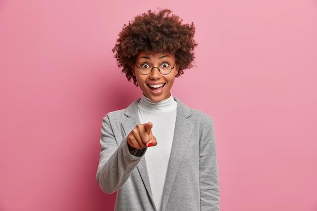 Довольная темнокожая женщина с афро-волосами указывает указательным пальцем прямо на вас