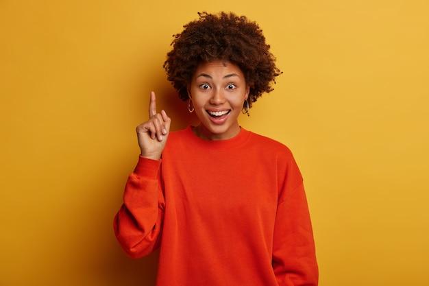 아프로 헤어 스타일을 가진 기쁜 어두운 피부의 여성은 멋진 제품을 추천하고 만족스러워하며 완벽한 프로모션을 보여주고 빨간색 스웨터를 입고 노란색 스튜디오 벽 위에 절연되어 있습니다.