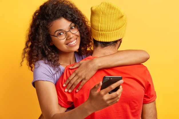 아프로 헤어 스타일을 가진 기쁜 어두운 피부의 여성은 둥근 안경을 쓰고 노란 모자와 빨간 티셔츠를 입은 남자를 안고 휴대 전화를 들고 중요한 전화를 기다립니다. 사람, 기술, 관계 개념