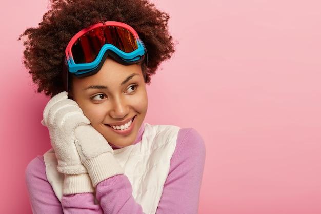 아프로 헤어 스타일을 가진 기쁜 어두운 피부의 여성, 스노우 보드 고글, 흰색 부드러운 장갑 착용, 겨울 스포츠 즐기기, 행복하게 외모, 분홍색 배경 위에 절연, 장난스럽고 기쁘게 느낍니다.