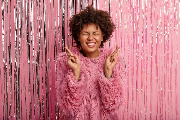 Felice giovane femmina dalla pelle scura con un ampio sorriso, indossa un cappotto rosa alla moda, incrocia le dita