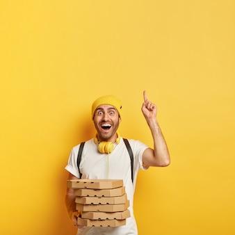 Радостный доставщик с коробками для пиццы