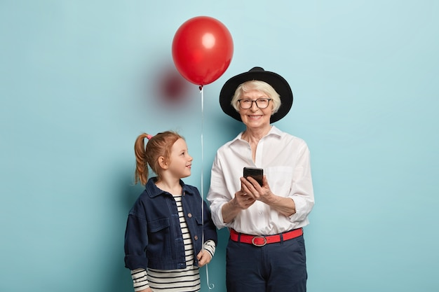 Glad elderly lady messages in online chat, being always in touch, wears stylish outfit. attractive red haired girl with ponytail, holds red balloon, congratulates granny with anniversary birthday