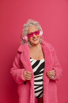 Glad elderly woman wears fashionable coat, follows fashion trends, enjoys music