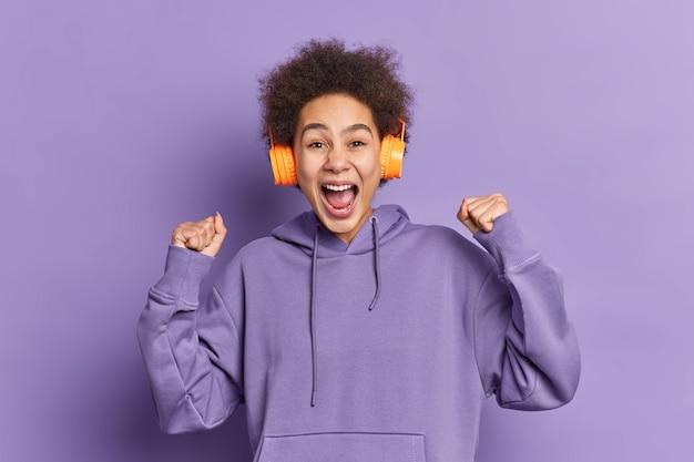 Радостная эмоциональная кудрявая девушка поднимает сжатые кулаки, радуется победным возгласам, слушает любимую музыку через беспроводные наушники, одетая в толстовку.