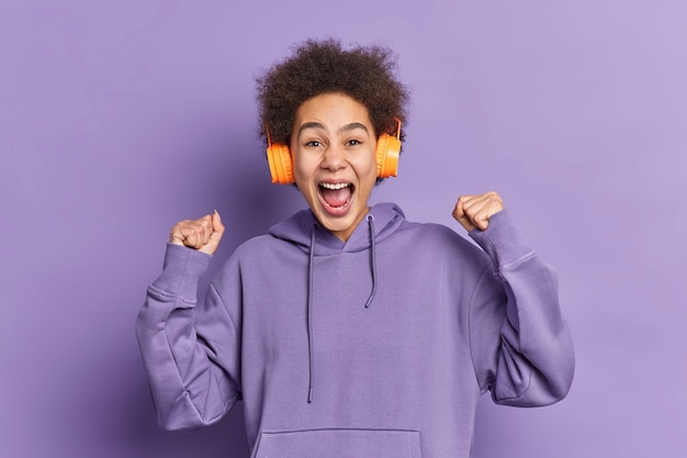 Glad emotive curly haired girl raises clenched fists celebrates winning exclaims with joy listens favorite music via wireless headphones dressed in sweatshirt.