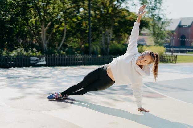 Радостная энергичная темноволосая женщина стоит на боковой доске, держит руку поднятой, укрепляет основные мышцы, улучшает стабильность, тренируется, носит спортивную одежду, наслаждается солнечным днем. концепция выносливости
