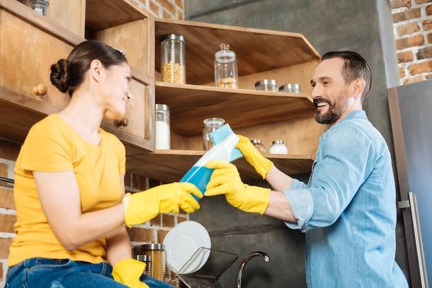 嘲笑しながらキッチンを掃除する熱狂的な若いカップルとクレンザーを与える妻