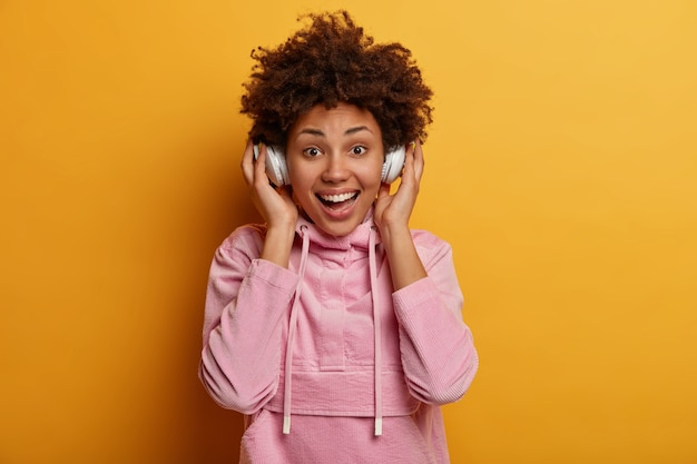Glad ethnic teenage girl in positive mood listens music via modern headphones, looks happily , enjoys good pure sound, spends leisure time listening favorite songs, dressed casually
