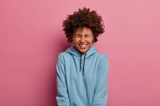 嬉しいエスニック女性が笑って顔を細くし、白い歯を見せながら笑顔を広げます
