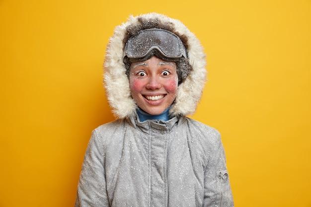 붉은 서리가 내린 뺨을 가진 기쁜 민족 여성이 행복하게 따뜻한 재킷을 입은 추위를 느낍니다.