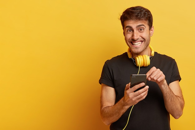Довольный европейский мужчина показывает на экран смартфона, носит желтые наушники и повседневную черную футболку