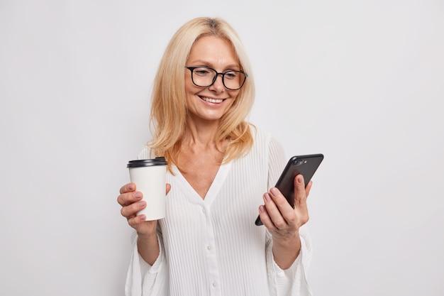 La donna europea contenta beve il caffè dalla tazza da asporto tiene lo smartphone utilizza la connessione internet gratuita durante la pausa sorride indossa delicatamente gli occhiali e la camicetta elegante isolata sul muro bianco