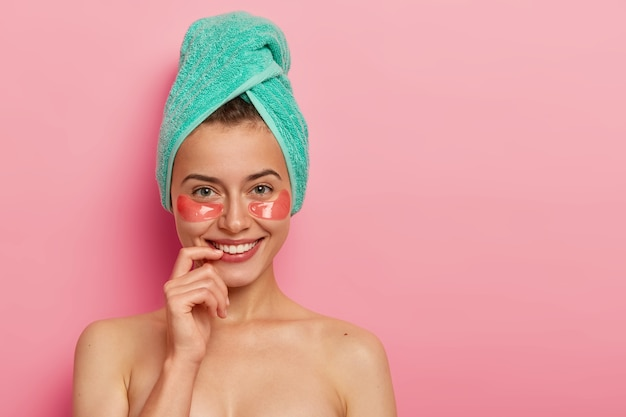 Glad european woman takes care of delicate skin around eyes, applies collagen patches, wears minimal makeup, wrapped bath towel on head, stands naked against pink background.