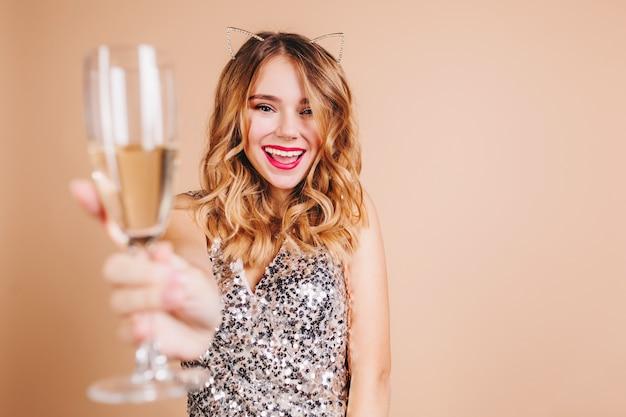 가벼운 벽에 미소로 와인 잔을 올리는 금발 곱슬 머리를 가진 기쁜 유럽 여성